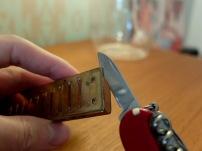 Heb mit dem Taschenmesser die Ecken der Stimmplatten EIN WENIG hoch.